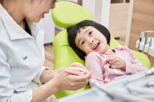 歯医者さんで笑顔で説明を受ける女の子